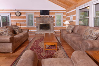 Pigeon Forge Two Bedroom Cabin Rental featuring a livingroom area that has a wood burning fireplace flat screen television and comfortable new sleeper sofa