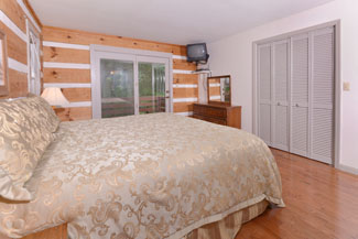 Pigeon Forge Two Bedroom Cabin Master Bedroom with a King Size Bed, also has access to a private outdoor deck area overlooking a wooded view.