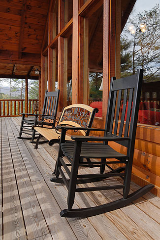 cabin with outdoor rockers overlooking a view