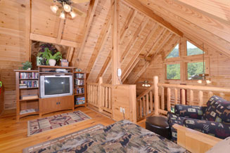 Pigeon Forge One Bedroom Cabin Rental that feautres a loft overlooking the livingroom and kitchen area