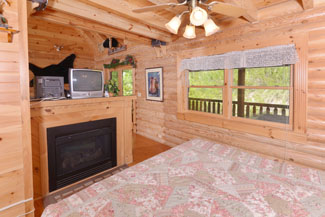 Pigeon Forge Cabin Rental Open bedroom with a gas fireplace in the main level living room area