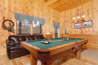 Gameroom area that features a gas fireplace sleeper sofa and a pool table