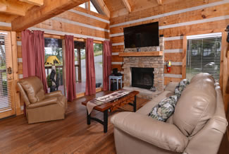 Pigeon Forge One Bedroom Plus Loft Cabin Rental Livingroom Area that features a Theater System-Foosball Table-Gas Fireplace- Mountain View
