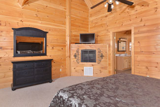 Pigeon Forge TN Vacation Cabin Rental that features an upstiars masterbedroom with a flat screen television
