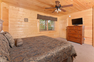 Pigeon Forge Vacation Cabin Bedroom with a flat screen tv and a king size bed