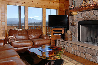 Living room area with a fireplace overlooking the kitchen and dinning area and a mountain view