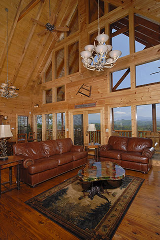 Living room area with a fireplace overlooking a Smoky Mountain View. Deluxe Leather furniture is in the living room area.