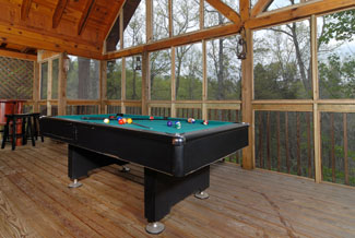 Tennessee Vacation Cabin Rental with an outdoor pool table on a screened in back porch that also features a hot tub