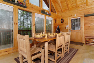 Pigeon Forge Two bedroom Cabin with a wooded view and a fireplace view from the 8 person dinning room table