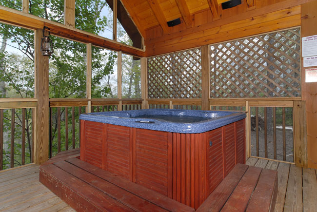 Outdoor hot tub off of the main level master bedroom that has a screened in back porch and privacy sheilds