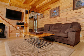 Pigeon Forge Cabin with a wood interior living room with pull out sofa sleeper and 2 recliners viewing a gas fireplace and a flat screen tv