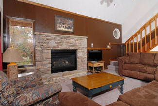 Pigeon Forge Chalet With microfiber Couches in the Living Room Area that has a Gas Fireplace