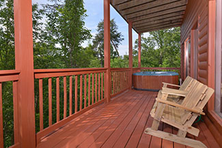Pigeon Forge Lower Level Deck Area that has a Hot Tub Rocking Chairs and a bench