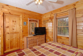 Pigeon Forge Cabin Bedroom that features a flat screen tv for your own private television enjoyment