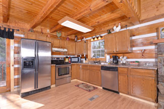 Pigeon Forge Tennessee Three Bedroom Cabin Rental that features a fully equipped kitchen with stainless steel appliances and large area