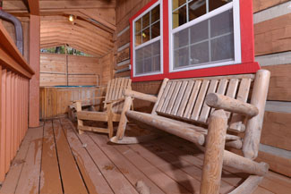 Pigeon Forge Three Bedroom Convenient Cabin Rental with a wooded view from the covered deck and log furniture