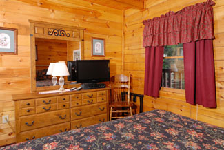 Cabin bedroom that features a television