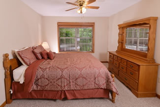 Two Bedroom Cabin Rental Queen Size Bed in the Bedroom with a View to the covered porch