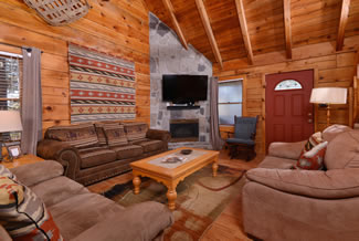 Gatlinburg Cabin Rental with a Cozy Livingroom setting with a Flat Screen Television and Gas Fireplace