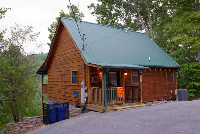 Pigeon Forge Cabin that has an indoor movie theater hot tub and a screen in back porch