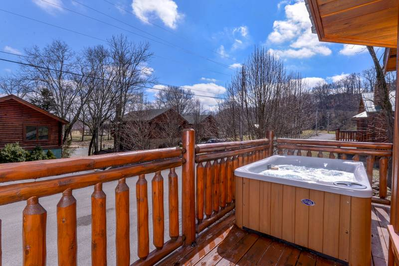Pigeon Forge Cabin Rental featuring a hot tub on the deck near the Little Pigeon River
