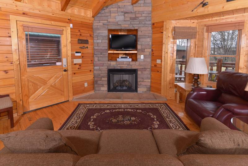 Pigeon Forge Cabin Rental Living Room Area that features a gas fireplace-flat screen television-sleeper sofa