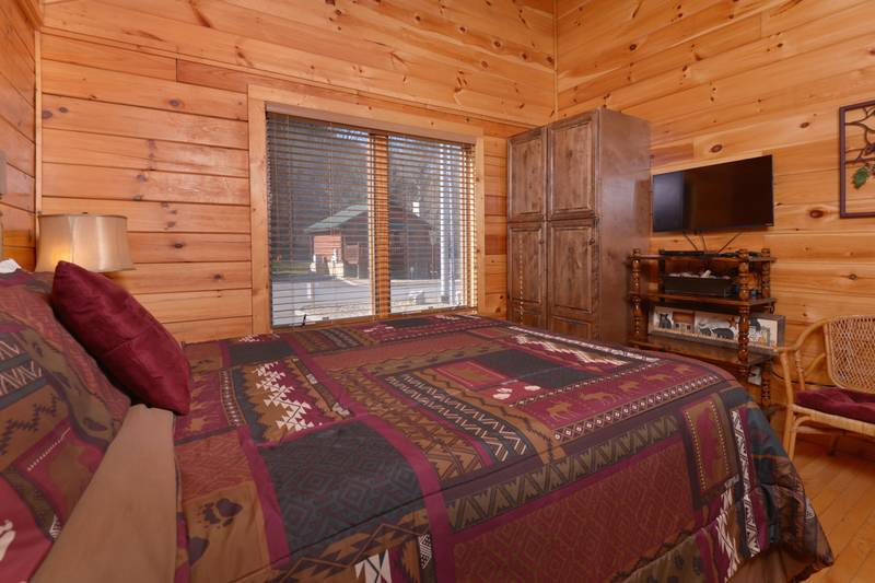 Tennessee Vacation Cabin Rental Queen Size Bed with a Flat Screen Television in the Bedroom
