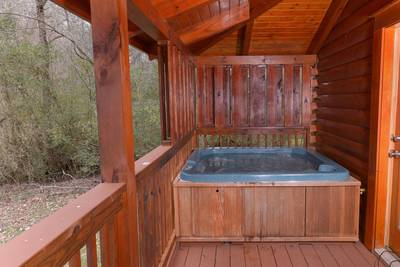 Pigeon Forge One Bedroom Cabin Rental featuring a hot tub on the deck overlooking the Little Pigeon River
